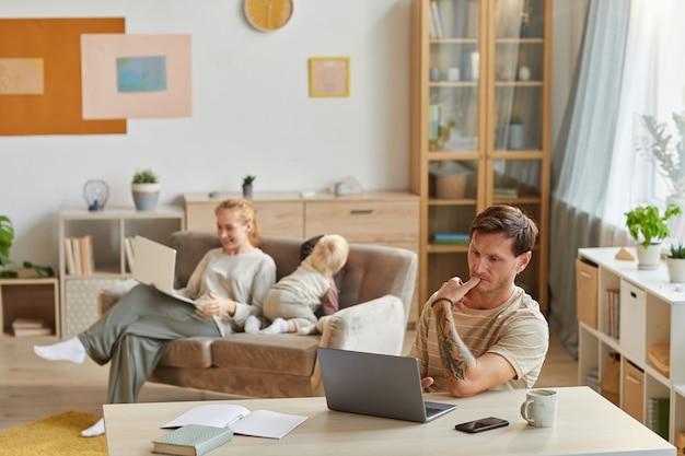Ernstige man zit aan de tafel en concentreert zich op zijn online werk op laptop met zijn gezin thuis