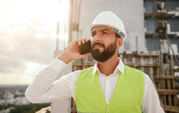 Ernstige mannelijke aannemer die op smartphone op bouwplaats spreekt
