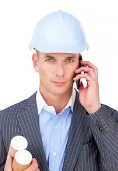 Ernstige mannelijke architect op telefoon