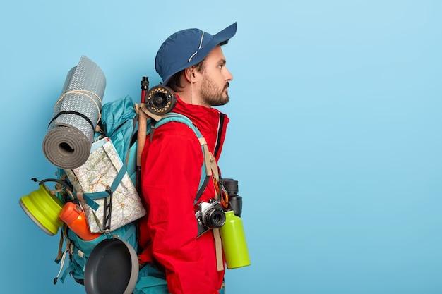Ernstige mannelijke backpacker staat met een grote rugzak, draagt veel noodzakelijke dingen om te reizen en uit te rusten, gaat alleen kamperen, verkent een nieuwe omgeving, gekleed in een rode jas en hoed