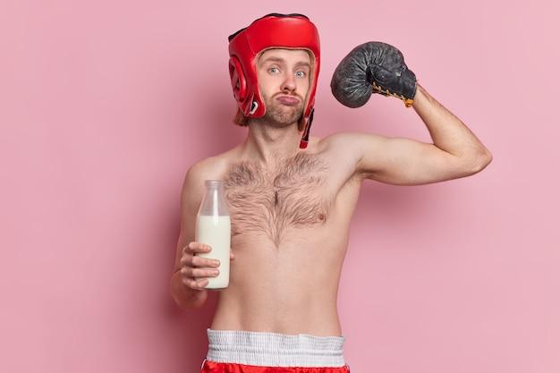 Ernstige mannelijke bokser heft arm op en toont spieren toont zijn kracht direct in de camera kijkt melk drinkt
