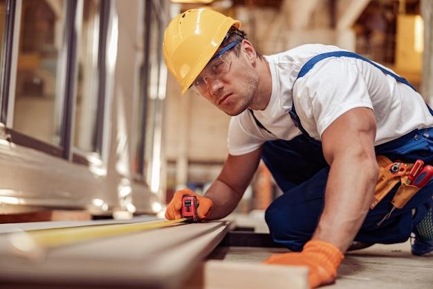 Ernstige mannelijke bouwer die houten plank meet op bouwplaats