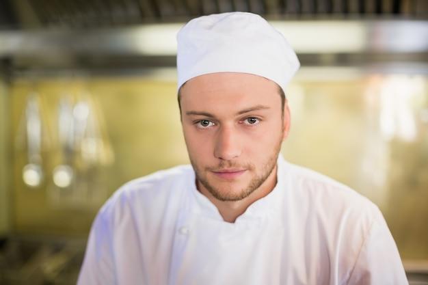 Ernstige mannelijke chef-kok in commerciële keuken