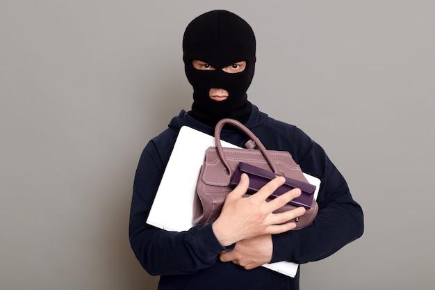 Ernstige mannelijke dief die een hoop gestolen dingen houdt