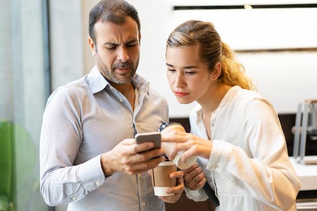 Ernstige mannelijke en vrouwelijke collega's die bericht op cellphone lezen