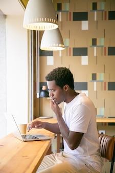 Ernstige mannelijke freelance die op laptop werkt en op cel in co-workingruimte spreekt
