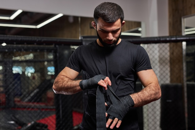 Ernstige mannelijke kickbokser vechter voorbereiden op gevecht, hand in verband wikkelen, klaar maken, gaan trainen en oefenen