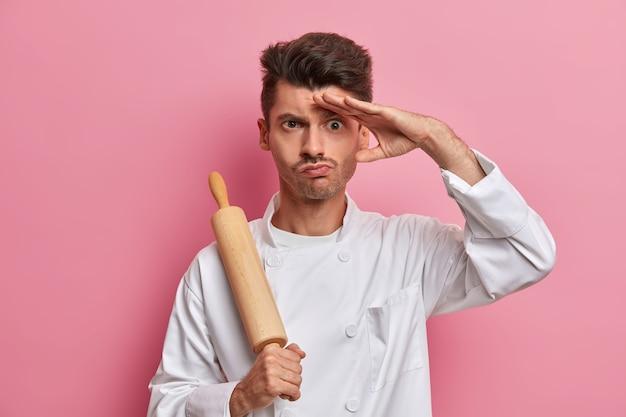 Ernstige mannelijke kok houdt deegroller vast, houdt de hand op het voorhoofd, bedenkt wat hij moet koken voor restaurantbezoekers