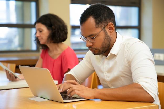 Ernstige mannelijke latijnse stagiair die in computerklasse werkt