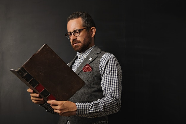 Ernstige mannelijke leraar in tweedvest en geruit overhemd die een groot oud boek op een schoolbord lezen