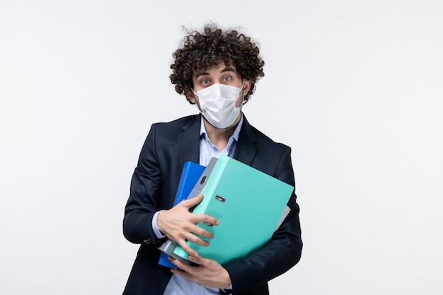 Ernstige mannelijke ondernemer in pak en het dragen van zijn masker met documenten op een witte ondergrond