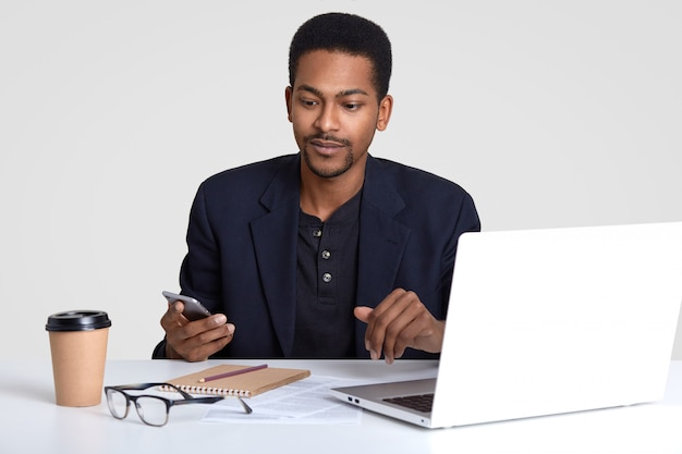 Ernstige mannelijke ondernemer met donkere huidskleur in formele kleding, heeft een mobiele telefoon, leest zakelijk nieuws op internet, werkt freelance, maakt aantekeningen in notitieblok, drinkt warme drank, poseert op het bureaublad.
