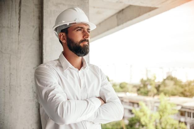 Ernstige mannelijke ondernemer tijdens een bezoek aan de bouwplaats