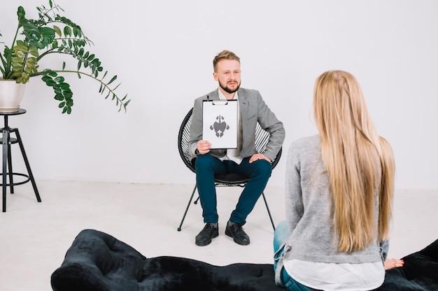 Ernstige mannelijke psycholoog die document met rorschach inkblot toont aan de vrouwelijke patiënt