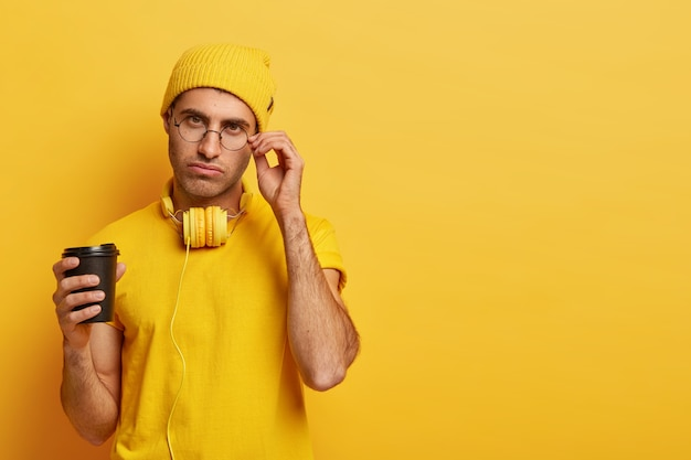 Ernstige mannelijke student houdt de hand op de rand van een bril, heeft een vermoeide uitdrukking