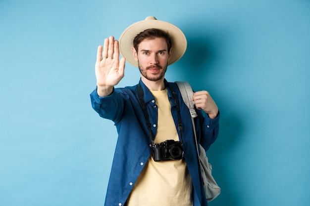 Ernstige mannelijke toerist waarschuwt u, strek uw hand uit om stopgebaar te tonen. man op vakantie verbiedt iets, weigert of verbiedt actie, staat met rugzak op blauwe achtergrond.