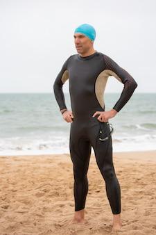Ernstige mannelijke zwemmer die zich op strand bevindt
