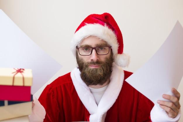 Ernstige mens die het kostuum van de kerstman draagt en document opheft