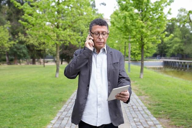 Ernstige mens gebruikend tablet en sprekend op telefoon in park