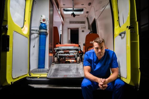 Ernstige mens in een medische iniforme zitting in de rug van een ambulanceauto