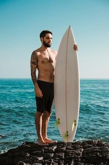 Ernstige mens met surfplank die zich op rots bevindt