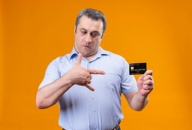 Ernstige middelbare leeftijd man in blauw gestreept overhemd creditcard kijken op een oranje achtergrond