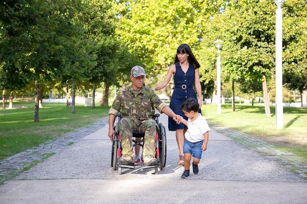 Ernstige militaire vader die in rolstoel met familie loopt. blanke vader van middelbare leeftijd in camouflage uniform zoon hand houden en praten met mooie vrouw. veteraan van oorlog en handicap concept