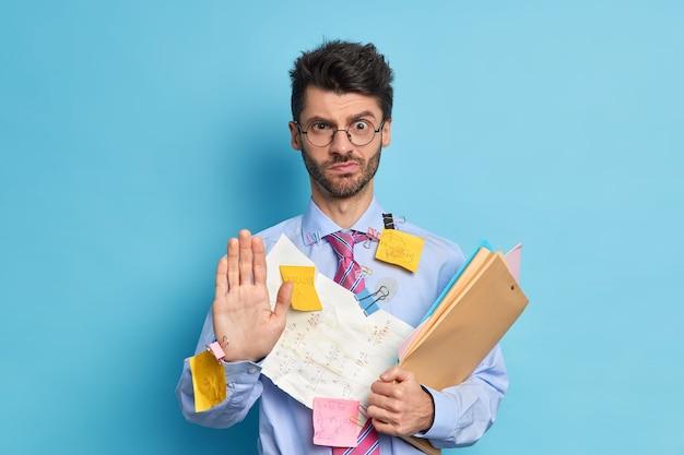 Ernstige mishandelde mannelijke werknemer zegt vasthouden handpalm naar camera in stopgebaar kijkt met strikte uitdrukking weigert je hulp bereidt projectwerk voor door hemzelf formeel gekleed