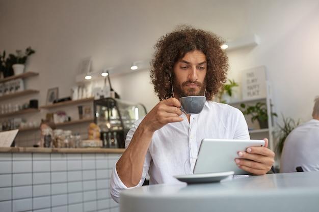 Ernstige mooie bebaarde man met krullend bruin haar zittend aan tafel in café en koffie drinken, tablet in de hand houden en oortelefoons dragen