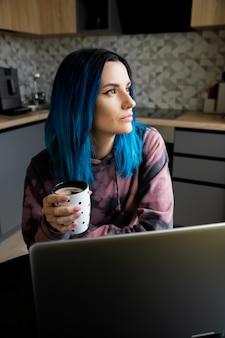 Ernstige mooie jonge vrouw die met blauw haar met laptop op keuken denkt