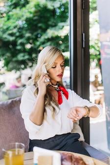 Ernstige mooie jonge vrouw die op de celtelefoon spreekt die haar polshorloge bekijkt