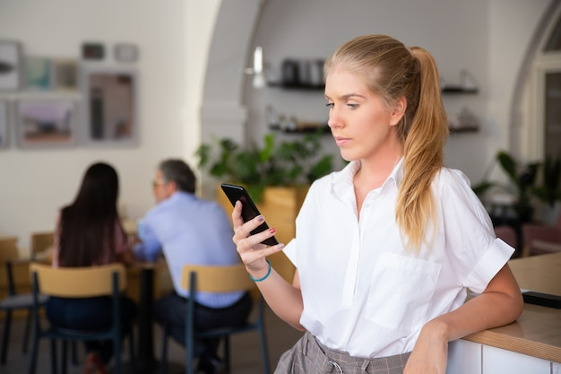 Ernstige mooie jonge vrouw die wit overhemd draagt, met behulp van smartphone, bericht aan het typen, die zich in co-werkruimte bevindt