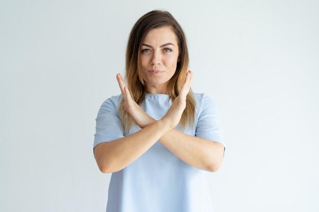 Ernstige mooie vrouw die gekruiste handen toont en camera bekijkt.