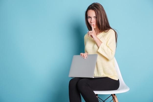 Ernstige mooie vrouw die stiltegebaar maakt met behulp van laptop geïsoleerd op de blauwe achtergrond