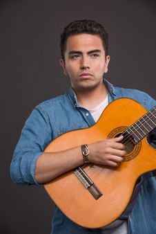 Ernstige muzikant gitaarspelen op zwarte achtergrond