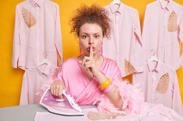 Ernstige mysterieuze huisvrouw met krullend haar maakt stiltegebaar en vraagt niemand te vertellen dat ze haar shirt heeft verbrand tijdens het strijken, omdat gebrek aan ervaring een kamerjas draagt die over een gele muur is geïsoleerd.