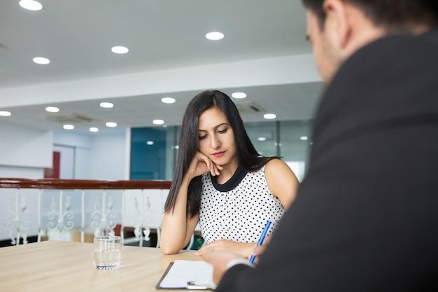 Ernstige nadenkende bedrijfsdame die aan strategische collega's luistert