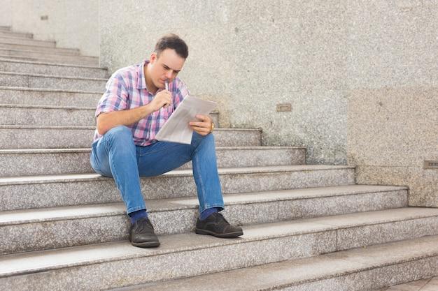 Ernstige nadenkende jonge mens die naar baan in krant zoekt