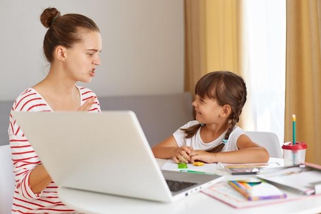 Ernstige nerveuze moeder legt thuistaak uit aan haar gelukkig lachende dochter, vrouw in casual kleding met haarverbod zittend aan tafel met schoolkind, voor open laptop en boek, online lessen.