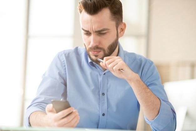 Ernstige of gespannen jonge officemanager die bericht of promo leest op smartphone die hij niet kan begrijpen