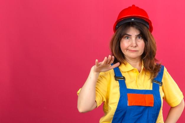 Ernstige ogende bouwer vrouw in bouw uniform en veiligheidshelm probeert kalmeren vriend die ongeveer fout maken staande met opgeheven palm vragen om te stoppen over geïsoleerde roze muur met agent