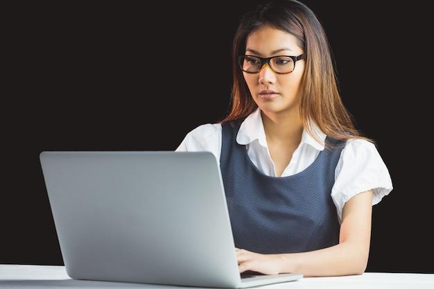 Ernstige onderneemster die laptop op zwarte achtergrond met behulp van