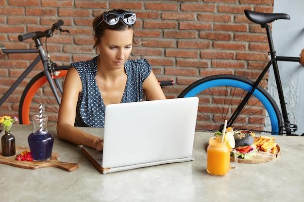 Ernstige onderneemster die met schaduwen op haar hoofd e-mail controleert op haar moderne laptop tijdens lunch in weekend. zelfstandige vrouw die notebook gebruikt voor werken op afstand