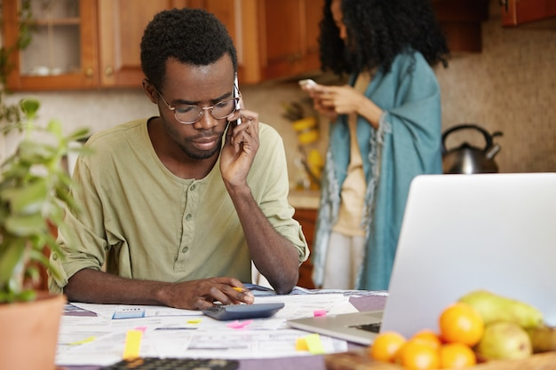 Ernstige ongelukkige afro-amerikaanse man met telefoongesprek tijdens het berekenen van gezinsbudget in de keuken