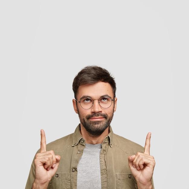 Ernstige ongeschoren blanke man met donkere haren, draagt een ronde bril, wijst met beide wijsvingers
