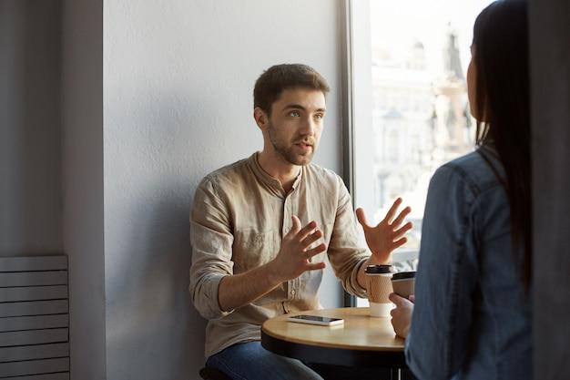 Ernstige ongeschoren donkerharige man zit in de kantine met cliënt, pratend en gebarend met handen, proberend enkele details te verduidelijken van de commissie die hij heeft ontvangen.