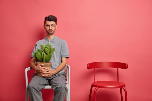Ernstige ontevreden blanke man in vrijetijdskleding rust in stoel houdt ingemaakte cactus blijft thuis