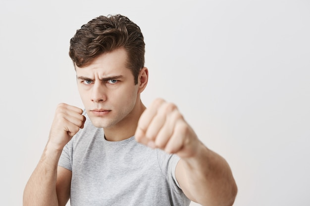 Ernstige ontevreden gespierde jonge blanke man fronst zijn gezicht in ongenoegen, toont gebalde vuisten, toont kracht en irritatie, geïrriteerd door iemand. negatieve emoties-concept.