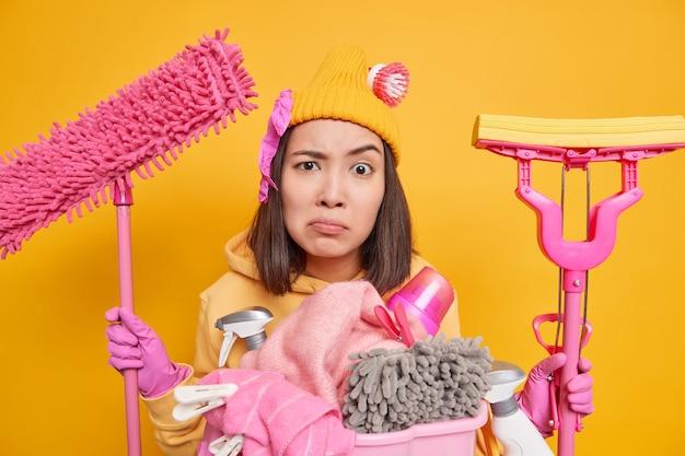 Ernstige ontevreden jonge aziatische vrouw doet voorjaarsschoonmaak kijkt nauwgezet naar camera draagt hoed hoodie rubberen handschoenen houdt twee dweilen in handen poses met wasmand en wasmiddelen binnen.