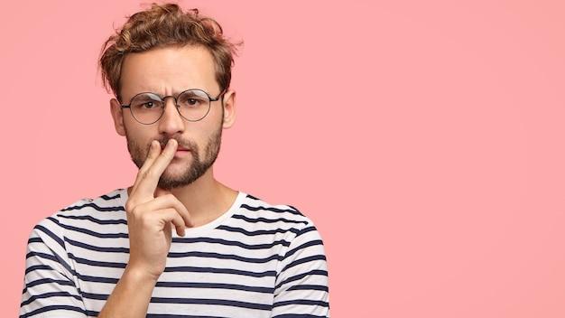 Ernstige ontevreden man fronst zijn wenkbrauwen, houdt de hand op de mond, heeft krullend haar en stoppels, draagt een gestreept t-shirt, een ronde bril